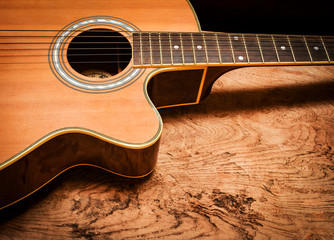 Vintage acoustic guitar on rustic wood background.