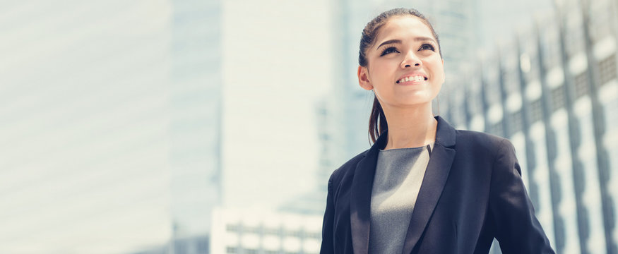 Young smiling Asian businesswoman on blur office building background