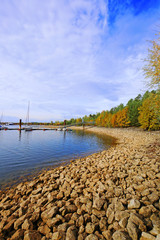 Autumn landscape on the lake. Rocky beach and mooring for boats . vertical