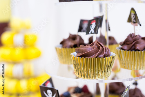 Close-up of cupcakes on stand in yellow and black colors, pirate theme for kids birthday party