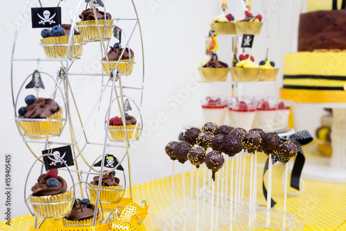 Assortment of birthday party cakes in yellow and black color, pirate theme, for boy. Focus cakepops