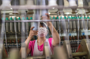 female worker standing beside thread making machine inside cotton mill,industry concepts.