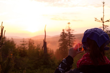 A young girl takes pictures of a mountain landscape at sunset