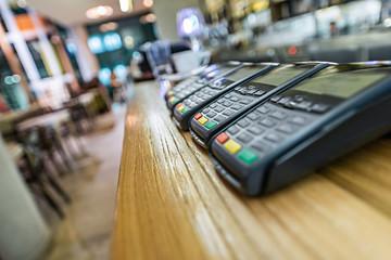 Credit card terminal in modern restaurant, blured background