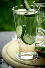 Cold drinking water in a glass with a cucumber on a wooden board