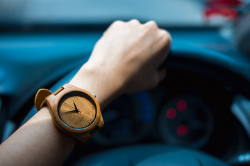 business woman hand wearing wooden wrist watch. her holding steering wheel car for driving and have car interface status are background.