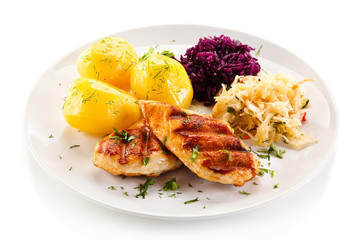 Grilled chicken fillet with boiled potatoes on white background