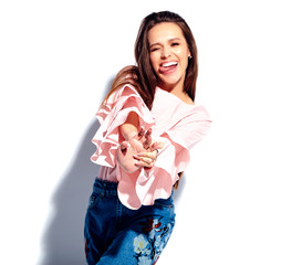 Portrait of beautiful caucasian smiling brunette woman model in bright pink blouse and summer stylish blue jeans with flowers print isolated on white background