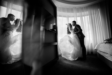 The bride and groom on the window background. Black and white photo