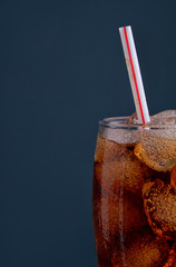 Cola in glass with straw and ice cubes on dark background