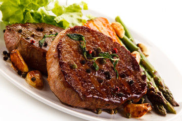 Grilled beef steaks with asparagus and carrots on white background