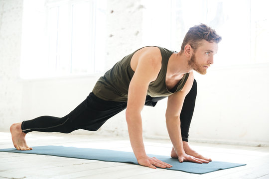 Handsome concentrated man doing yoga on mat