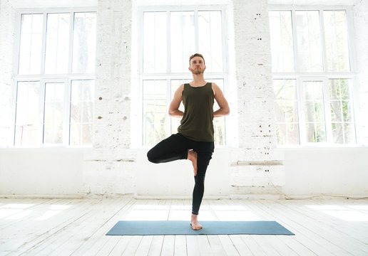 Young man doing yoga or pilates exercise