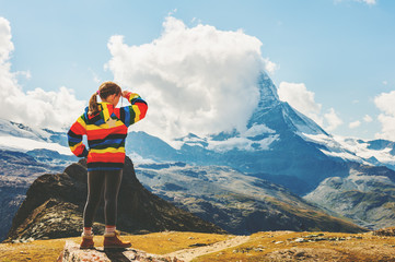 Cute little girl with arms wide open, wearing colorful coat, standing in front of Matterhorn mountain, Switzerland, back view