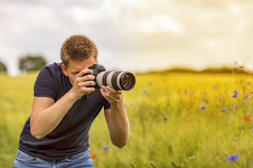 Young man shooting outdoor photos in the sun