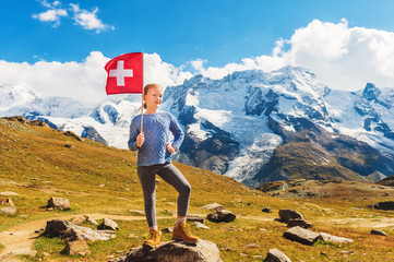 Cute little girl holding swiss flag, standing in front of Gornergrat glacier, Switzerland