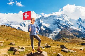 Cute little girl holding swiss flag, standing in front of Gornergrat glacier, Switzerland