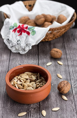 Vertical capture of pumpkin seeds in earthenware pot and walnuts in basket on wooden table