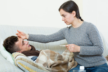 Concerned mother giving mixture to son with quinsy