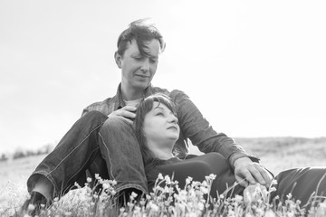 Affectionate young couple on the lawn in the park. Love story. Black and white.