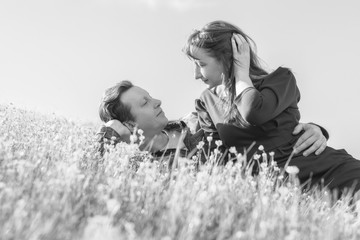 Affectionate young couple looking at each other on the lawn in the park. Love story. Black and white.