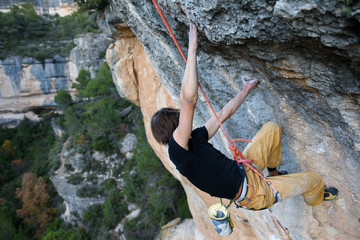 Rock climber ascending a challenging cliff. Extreme sport climbing. Freedom, risk, challenge, success. Sport and active