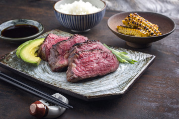 Japanese Kobe Steak Fillet with Rice and Avocado as close-up on a plate