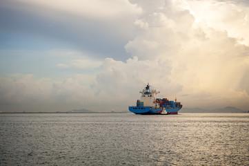 Cargo ship sailing away against sunrise