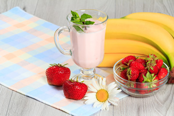 Glass of yogurt  with mint and fresh strawberries, banana, chamomile on the table