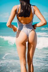 Beautiful brunette woman with perfect body standing up on beach, wearing stylish bikini and blue ocean
