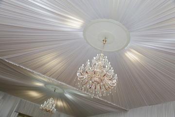 grand lustre avec pampilles et plafond blanc en tissu dans salle cérémonie mariage