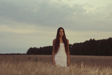 Sad lonely young girl in a field bored with depression