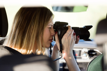 Beautiful young woman taking photos from the car.