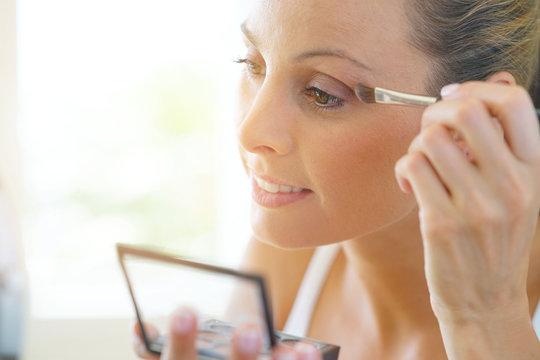 Young woman applying eyeshadow on