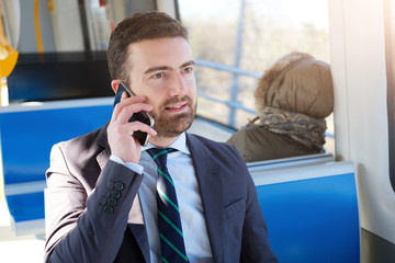 Businessman commuter is traveling and is talking on the mobile phone
