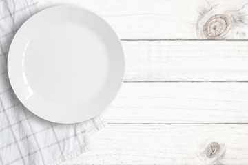 Top view of empty food plate put on tablecloth and wood table., All white object with copy space.