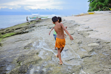 two little asian boys splashing their feet in shallow water ahead of oncoming waves of the sea at sunset, Island, Philippines