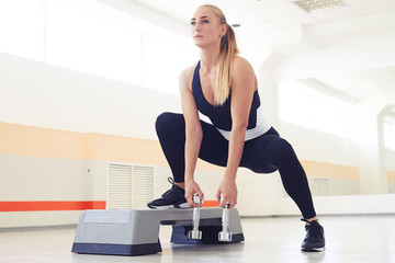 Determined woman exercising step aerobics with hand weights
