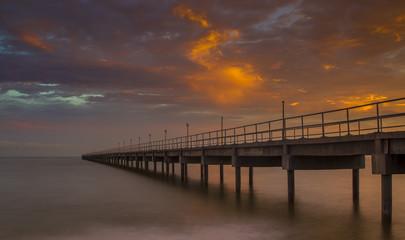 Bridge against sun setting clouds