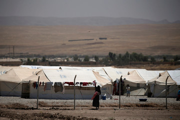 A displaced Iraqi woman gathers her laundry at the Hasansham U2 camp where more than 300 people fell ill in a mass outbreak of food poisoning, in al-Khazer, east of Mosul