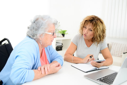 mature woman helping assisted elderly senior female with administrative procedures and paperwork on internet with a laptop computer at home