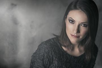 Beautiful woman with dark hair and hazy eyes looking at camera.