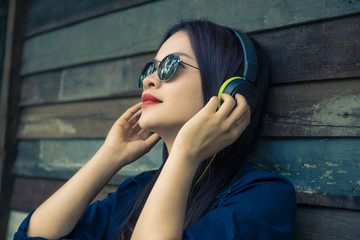young happy asian woman using headphone to listen to her music