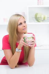 Hübsche Hausfrau in Gedanken an der Küchentheke