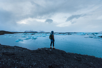 Young attractive man standing all alone among blue icebergs in the glacial lake in the south Iceland