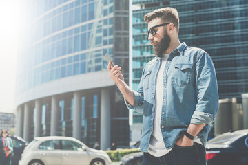 Young bearded businessman in sunglasses stands on city street and uses smartphone. In background is modern building