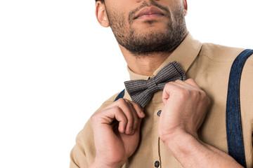 Cropped shot of stylish bearded man adjusting bow tie isolated on white