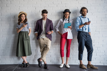 young stylish friends using digital devices while standing near brick wall