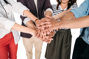 Cropped shot of young friends putting hands together isolated on white
