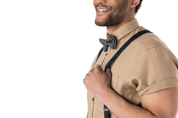 Cropped shot of smiling young man in suspenders and bow tie posing isolated on white